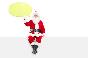 Santa Claus holding a big yellow speech bubble