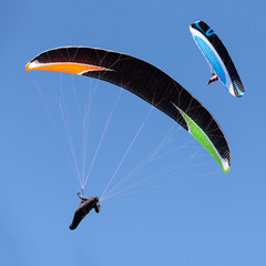 Two paragliders in flight against blue sky