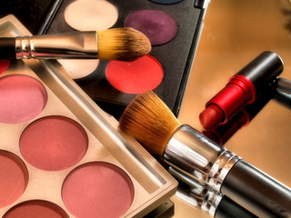 Make up color palette with red lipstick and brushes.