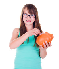 Teen girl putting coin into piggy bank