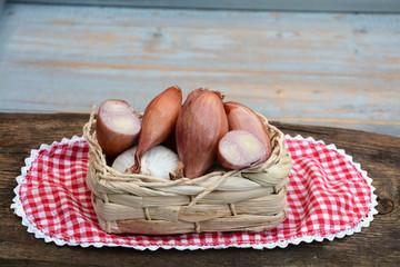 sjalotjes,knoflook en uien in een mandje met kleedje