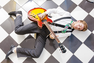 fifties style - young guitarist playing lying on the floor