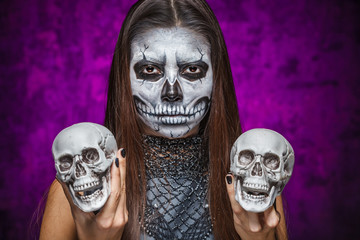 Young woman in day of the dead mask skull face art with two skul