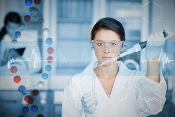 Serious chemist working with large pipette