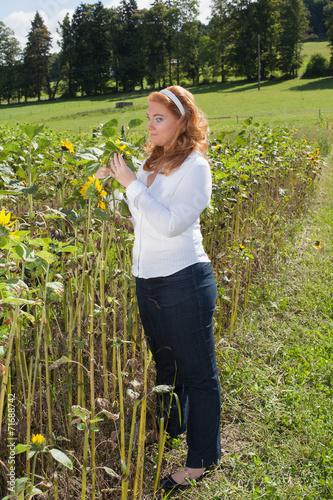 canvas print picture Schöne rothaarige Frau auf einem Sonnenblumenfeld.