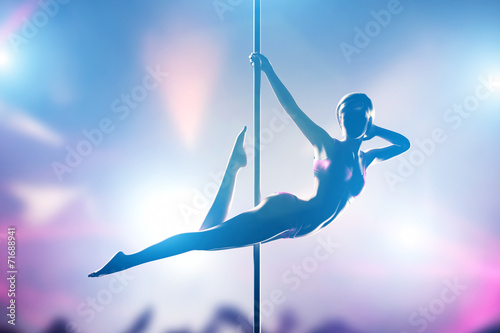 canvas print picture Woman performs pole dance in night club. Sexy body silhouette