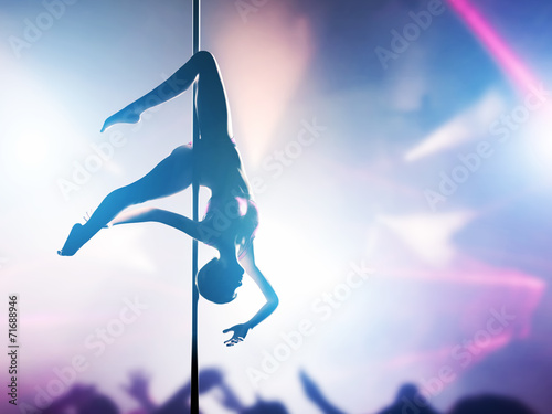 Woman performs pole dance in night club. Sexy body silhouette - 71688946