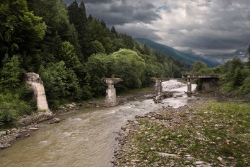 The destroyed bridge through the river Pruth in the Carpathians,