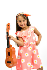 Happy little girl playing a guitar