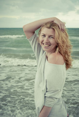 Portrait of beautiful laughing red-haired girl on the seaside.