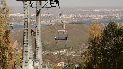 Ropeway against the city an autumn sunny day