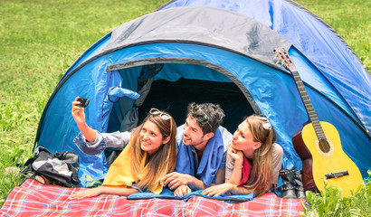 Group of best friends taking a selfie while camping together