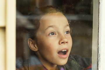happy little girl looking through an old window