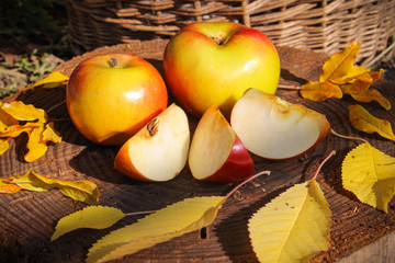 Apples and yellow leaves on the wooden background