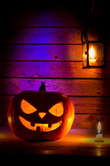 Halloween pumpkin with a lantern and a candle on wooden backgrou