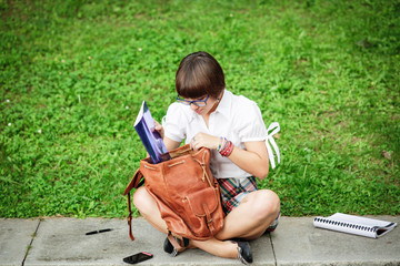 Girl studying on green grass
