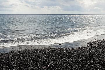Black pebbles and sea