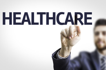 Business man pointing to transparent board with text: Healthcare
