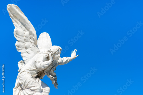 Papiers peints Statue Beautiful angel on a clear blue sky with space for text