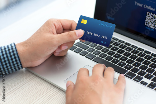 Fototapeta man doing online shopping with credit card on laptop