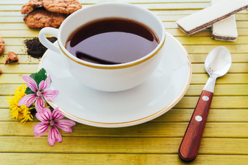 Cup of english tea with assorted chocolate cookies