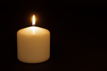 White candle burning against a black background