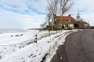 Coast of Dutch village Urk in wintertime with church and houses