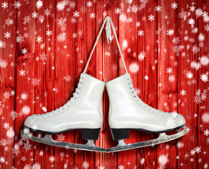 Pair of White Ice Skates on red wooden backround