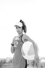 Sporty woman drinking water against the sky