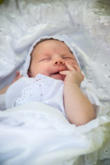 Little Newborn Sleeping over Her White Bed on white background