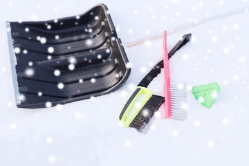 black snowshowel with wooden handle in snow pile