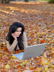 Pretty Smiling Woman Lying on Ground with Laptop