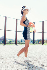 Sporty woman with color ball drinking water