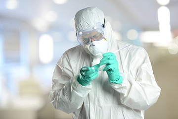 Scientist in protective hazmzt suit working in laboratory
