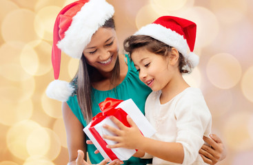 happy mother and girl in santa hats with gift box