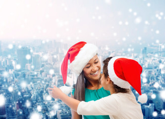 happy mother and girl in santa hats