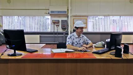 engineer in white helmet at large table, speaking on phone