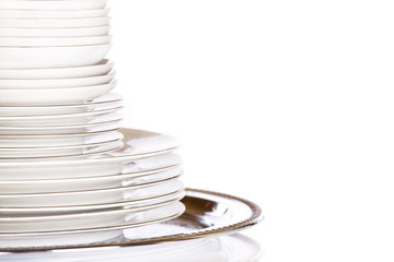 Stack of white dishes on silver platter