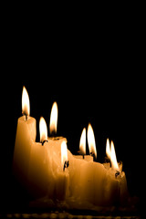 Group of white candles burning in the dark