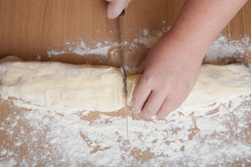 hand with a knife cut dough for rolls