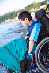 Disabled little boy in wheelchair down by water on beach