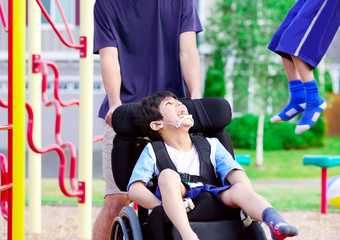 Disabled boy in wheelchair enjoying watching friends play at par
