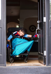 Disabled boy in wheelchair opening front door