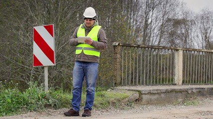 ngineer with tablet PC near the bridge defence barriers