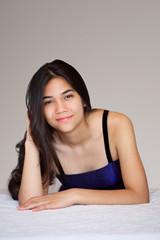 Beautiful biracial teen girl lying down, relaxing