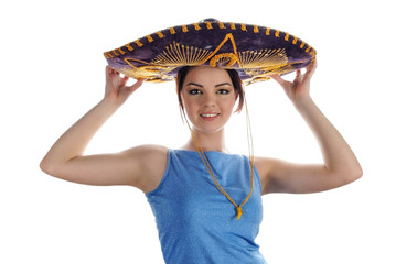 Young smiling girl trying on Mexican sombrero.