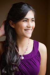 Beautiful biracial young woman in purple dress smiling off to si