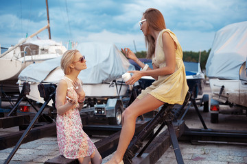Two beautiful young women are talking on pier