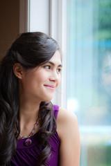 Beautiful biracial young woman smiling by window