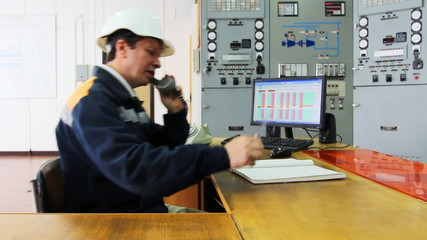 engineer talks by phone and writes data to working log